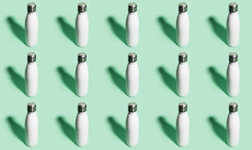 Viele Edelstahlflaschen auf hellgrünem Hintergrund